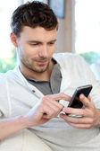 Young man using mobile phone to send short message — Stock Photo