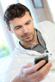 Young man using mobile phone with handsfree headset — Stock Photo