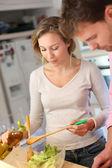 Couple enjoying preparing dinner in kitchen — Stock Photo