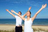 Couple méditant sur la plage avec les bras vers le haut — Photo