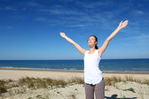 Mulher respirando com braços até à beira da praia — Fotografia Stock