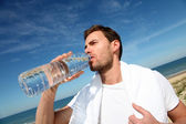 Portrait of jogger drinking water from bottle — Stock Photo