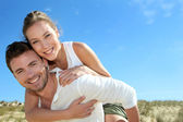 Man giving piggyback ride to girlfriend on a sand dune — Stock Photo