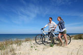 Couple standing on a sand dune with bicycles — 图库照片