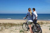 Couple standing on a sand dune with bicycles — Stock Photo