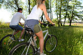 Couple riding bicycles in field by a lake — Foto de Stock