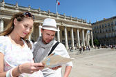 Couple holding a touristic map of Bordeaux — Foto de Stock