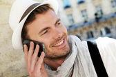 町に電話で話しているトレンディな男の笑みを浮かべてください。 — ストック写真