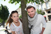 Couple standing by a tree in town — Stock fotografie