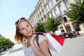 Mooie jonge vrouw in de stad houden shopping tassen — Stockfoto
