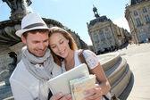 Paar staande door het place de la bourse met elektronische tablet — Stockfoto