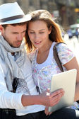 Couple in town using electronic tablet — Stock Photo