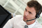 Portrait of salesman with headset on — Stock Photo