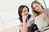 Women photographers working in office with tablet — Stock Photo