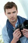 Handsome guy holding photo camera — Stock Photo