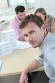 Portrait of man sitting in office with colleagues — Stock Photo