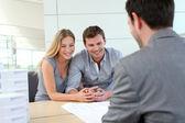 Couple en agence immobilière parler aux cartes de construction — Photo
