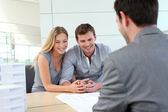Couple in real-estate agency talking to construction planner — Stok fotoğraf