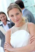 Beautiful businesswoman standing outside in front of team — Stock Photo