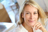 Portrait of blond mature woman relaxing in sofa — Stock Photo