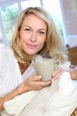 Mulher loira madura no sofá tomando um chá — Foto Stock