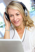 Middle-aged blond woman listening to music with tablet — Stock Photo