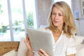 Beautiful mature woman using electronic tablet at home — Stock Photo
