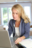 Middle aged blond woman working at home with laptop — Stock Photo