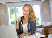 Attractive middle-aged woman working at home — Stock Photo