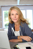Middle-aged blond woman working at home with laptop — Stok fotoğraf