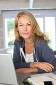 Orta yaşlı sarışın bir kadın evde laptop ile çalışma — Stok fotoğraf