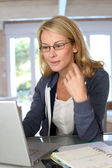 Middle-aged blond woman working at home with laptop — Photo