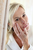 Attractive middle-aged woman applying comestics on her face — Stock Photo