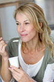 Portrait of middle-aged woman eating yoghurt — Stock Photo