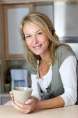 Attractive adult woman holding mug in home kitchen — Stock Photo
