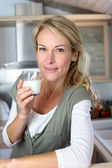 Portrait of blond woman drinking milk in home kitchen — Stock Photo