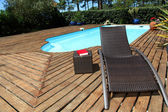 View of long chairs set by swimming pool — Stock Photo
