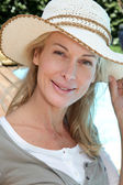 Portrait of smiling mature woman relaxing outside — Stock Photo