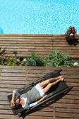 Woman relaxing in deck chair by swimming pool — Stock Photo