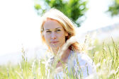 Beautiful woman standing in country field in summer time — Stock Photo
