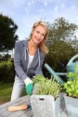 Donna in giardino pronto per innaffiare le piante fresche — Foto Stock