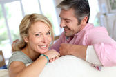 Middle aged couple relaxing in sofa at home — Stock Photo