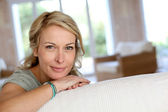 Beautiful blond mature woman relaxing in sofa — Stock Photo