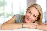 美丽的金发碧眼的成熟的女人的放松在沙发 — 图库照片
