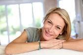 Beautiful blond mature woman relaxing in sofa — Stock Photo