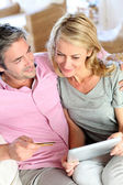 Couple sitting in sofa at home and doing online shopping — Stock fotografie