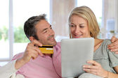 Couple sitting in sofa at home and doing online shopping — Stock Photo