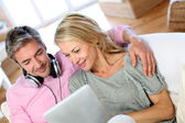 Couple listening to music at home with tablet — Stock Photo