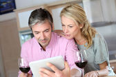 Couple in kitchen with glass of wine websurfing on tablet — Stock Photo