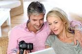 Couple at home looking at pictures on electronic tablet — Stock Photo
